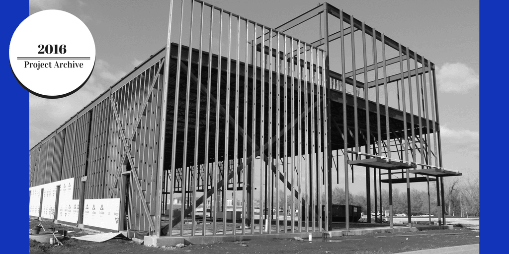 Image of a single story building under construction, which is framed in steel. In the upper left cor