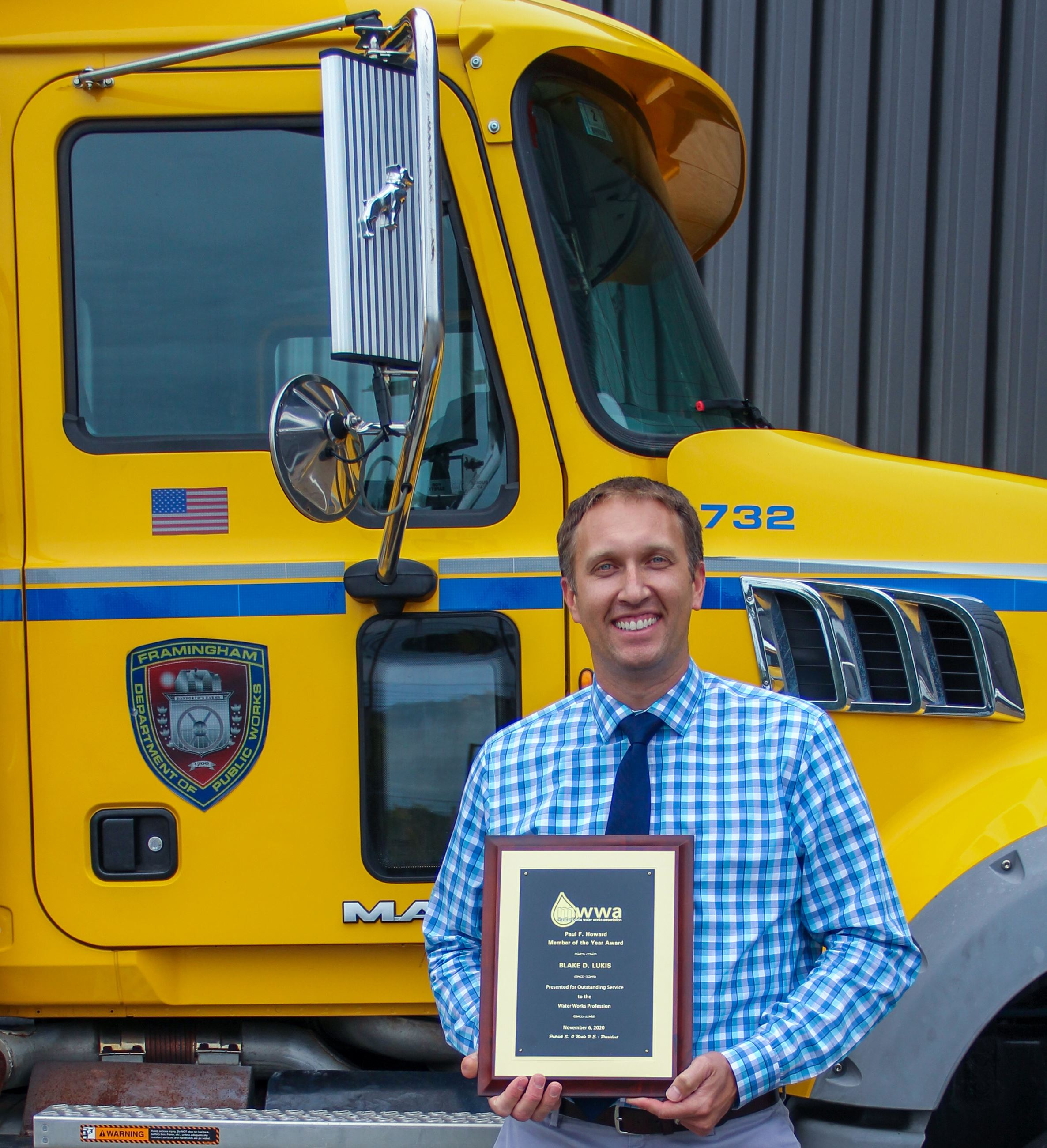 Photo of Blake Lukis holding a plaque from MWWA near a yellow Framingham DPW Truck