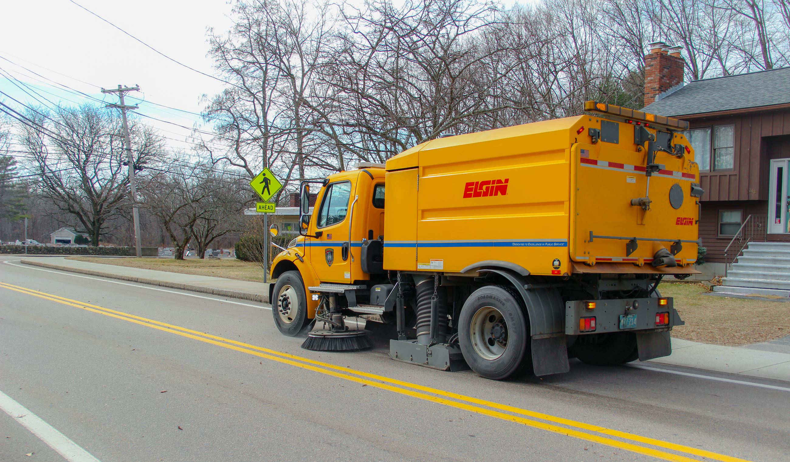 Photo of a yellow DPW Street Sweeper cleaning the road