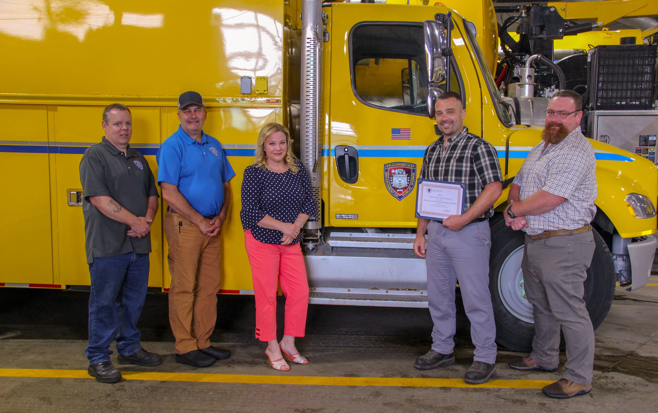 Image of the Water Department Management Staff and Operations Managers standing near a yellow truck