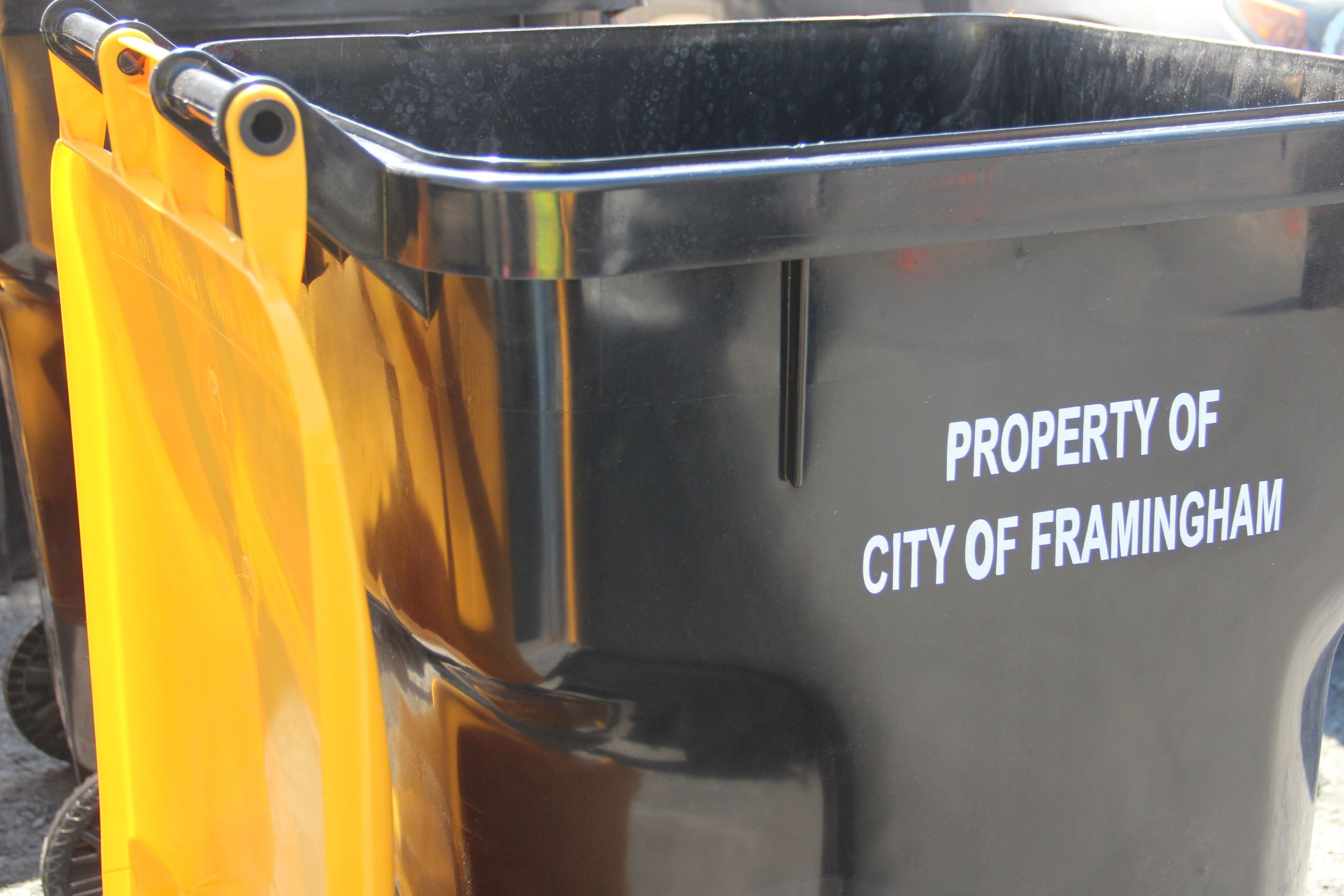 Image of a black and yellow recycling toter with text: Property of City of Framingham