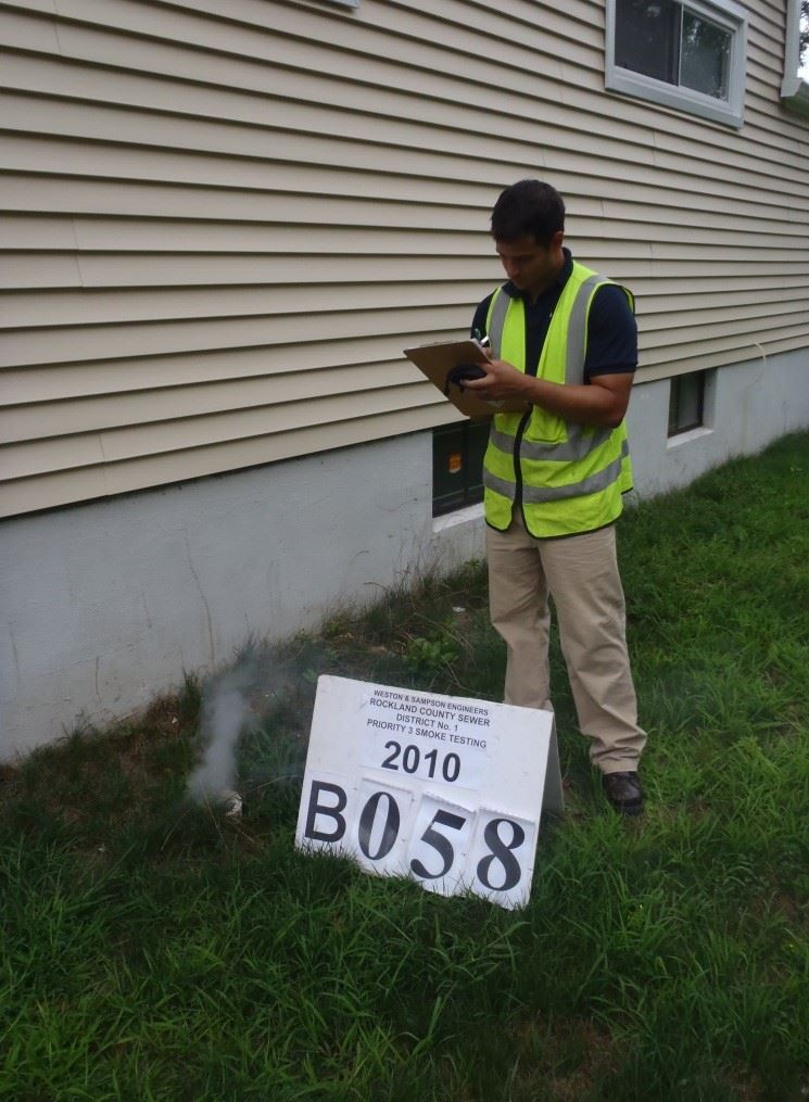 a worker recording a smoke defect photo